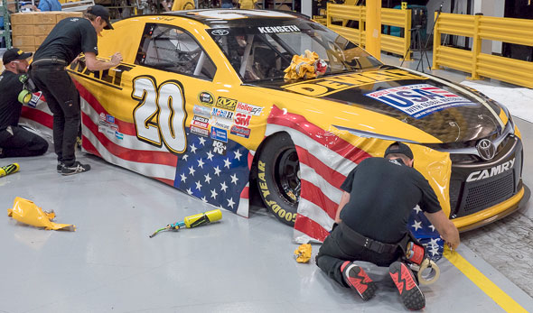 Dewalt Team Applying Decal Skin to NASCAR Car